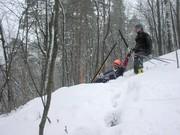 Андрей бредет по колено в снегу, попутно поднимая упавшие тела